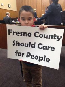 Ernesto, age 5, holds a sign during the Dec. 31 court hearing urging the Board of Supervisors to care for people. Photo by Veronica Garibay